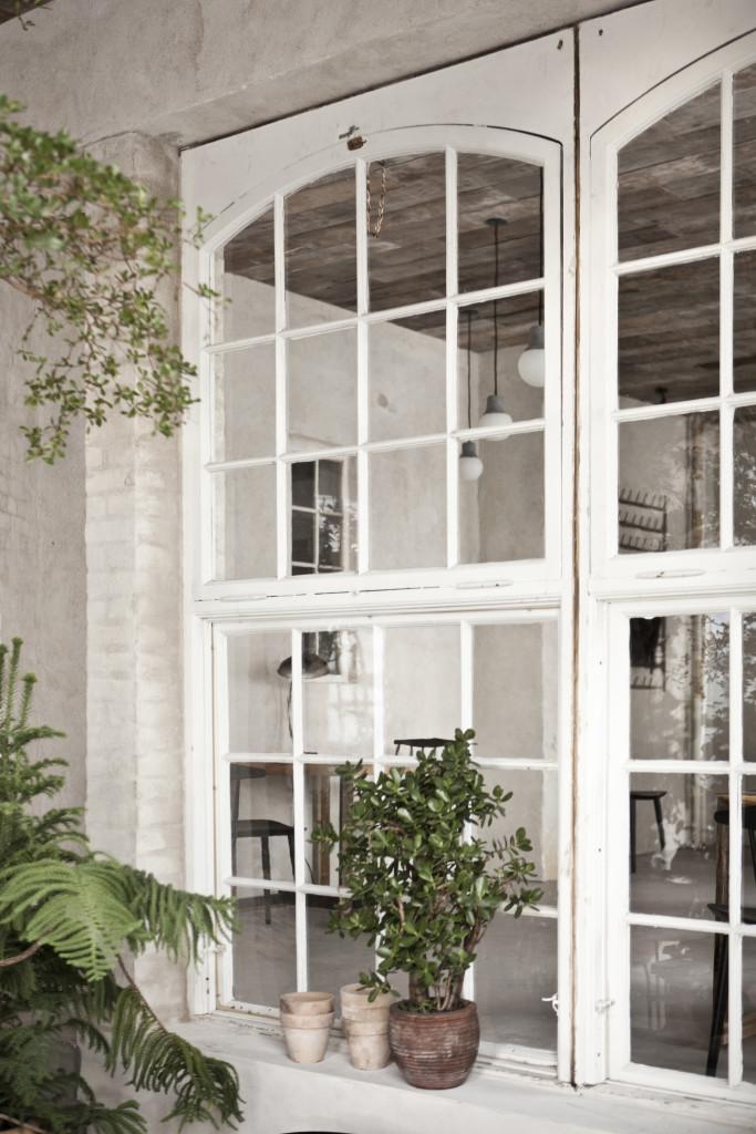 Disse småsprosset vinduer fra Øresundshospitalet skaber en særlig stemning i deres kontrast til de rå materialer, der ellers pryder restauranten. Vinduerne er købt hos Genbyg.