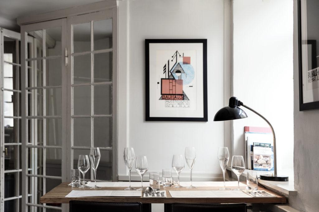 Det enkle og stilrene går igen i indretningen. Her ses den klassiske Christian Dell lampe, som er fundet hos Genbyg og brugte vinduer, der er blevet forvandlet til det fine indgangsparti.