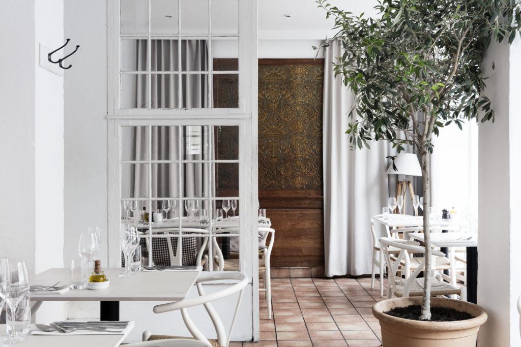 Vægpanel: De hvide møbler står flot i kontrast til det mørke træ på det gamle vægpanel. Panelet får nærmest et eksklusivt look i sin indramning af de lyse gardiner.