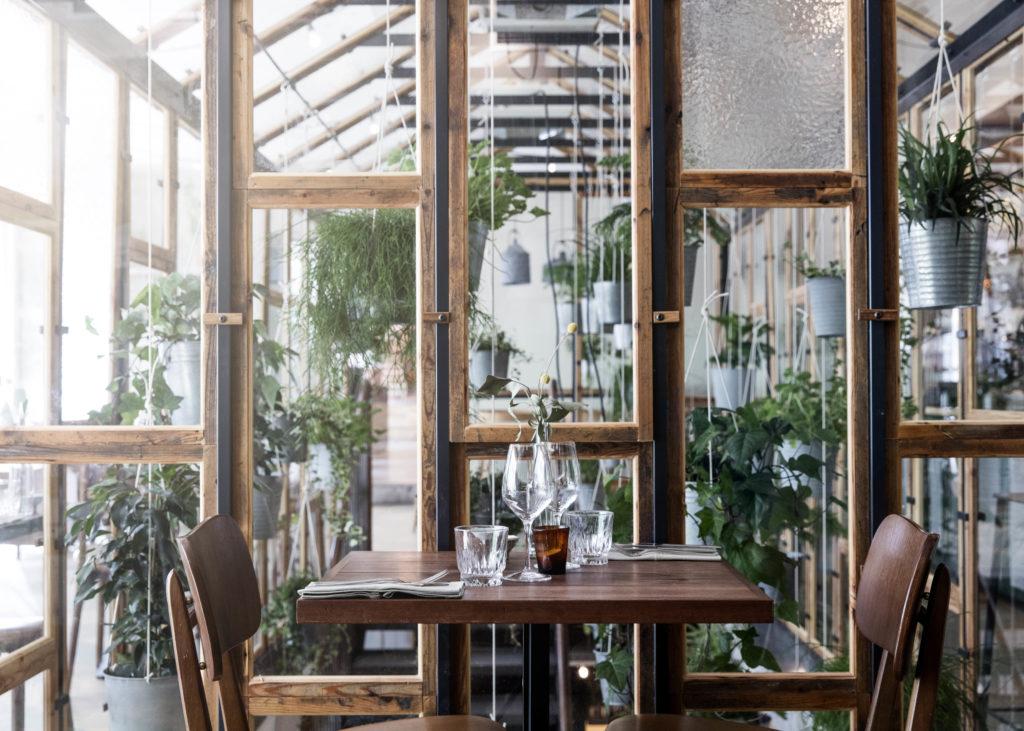 Drivhuset giver et organisk udtryd og forbinder restaurantens to etager. Alle mahognilister er lavet ud af den gamle tribune på Lyngby Stadion.
