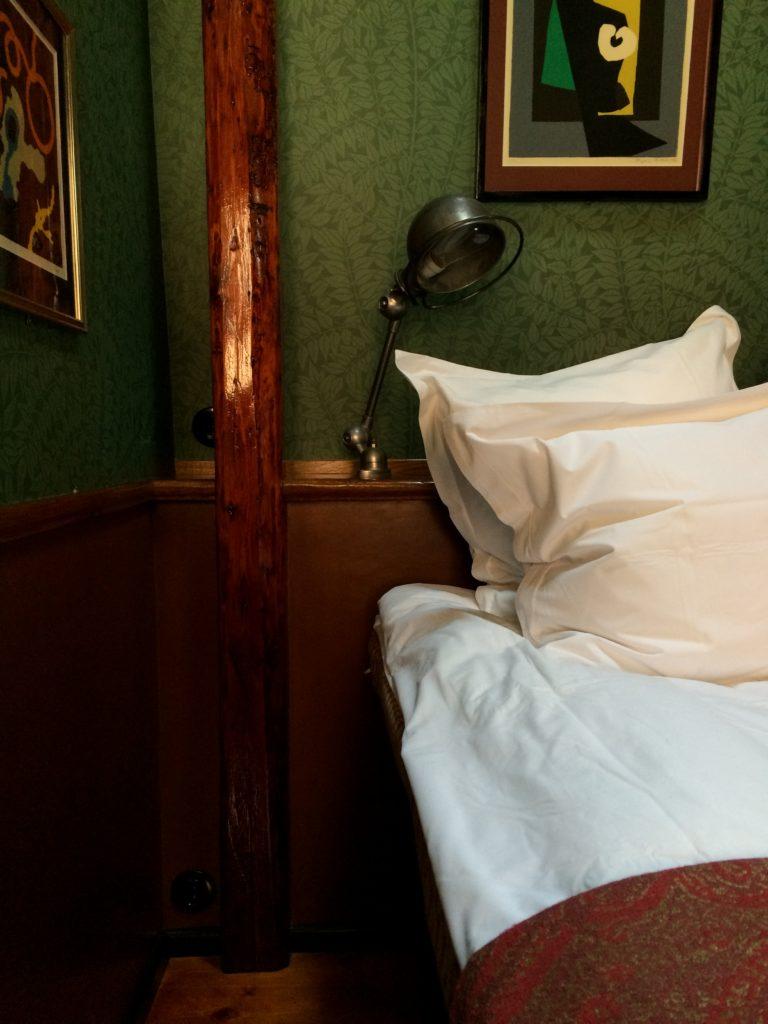 Det gamle træ er et gennemgående element på det lille værelse og står smukt med de grønne tapetserede vægge.